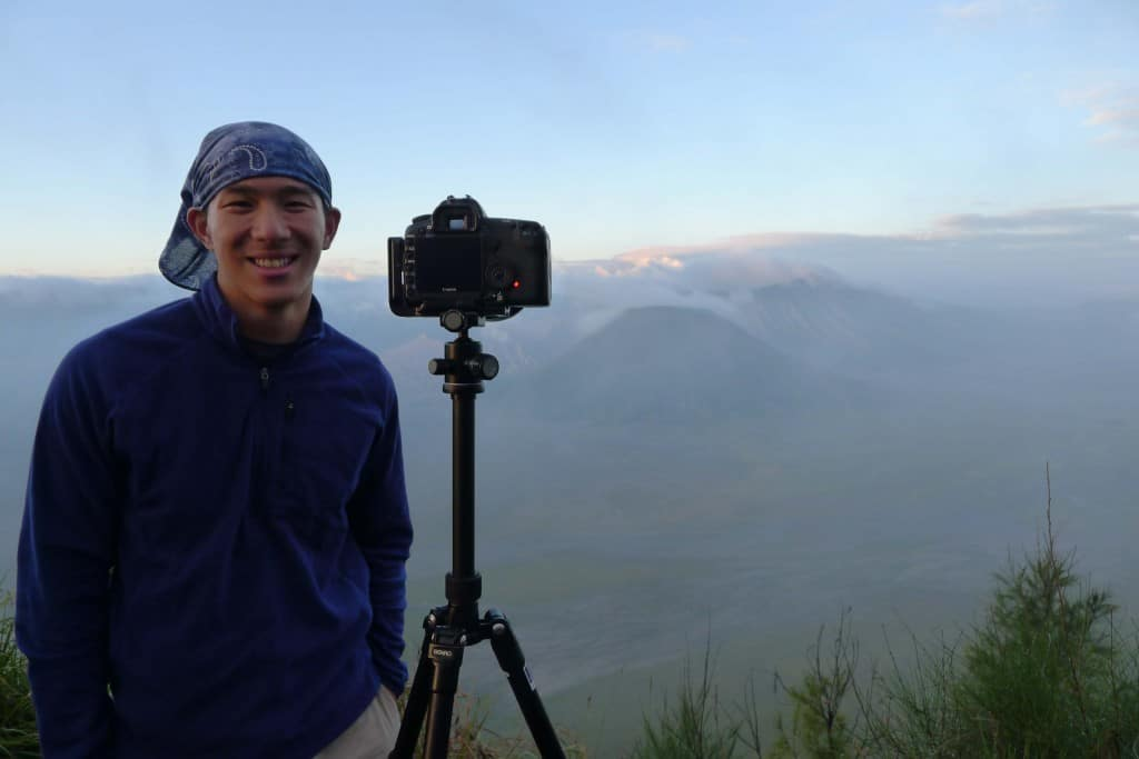 wearing the original buff headwear with tripod and camera and landscape behind