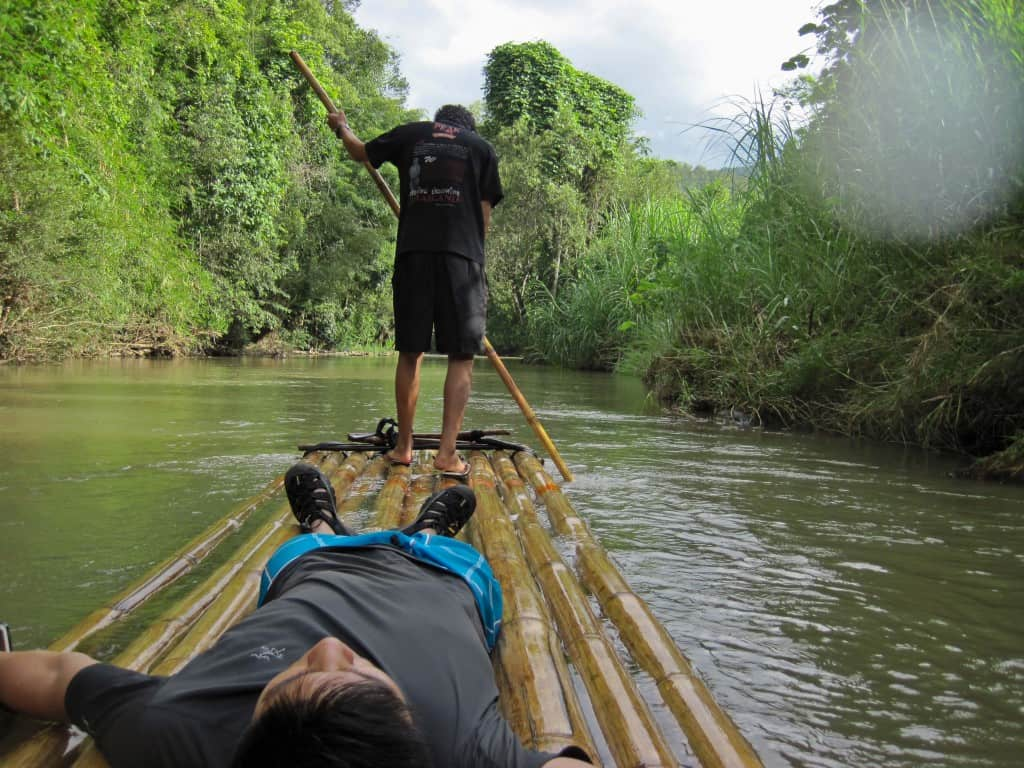 chiang mai bamboo rafting with man lying down and pilot manning raft