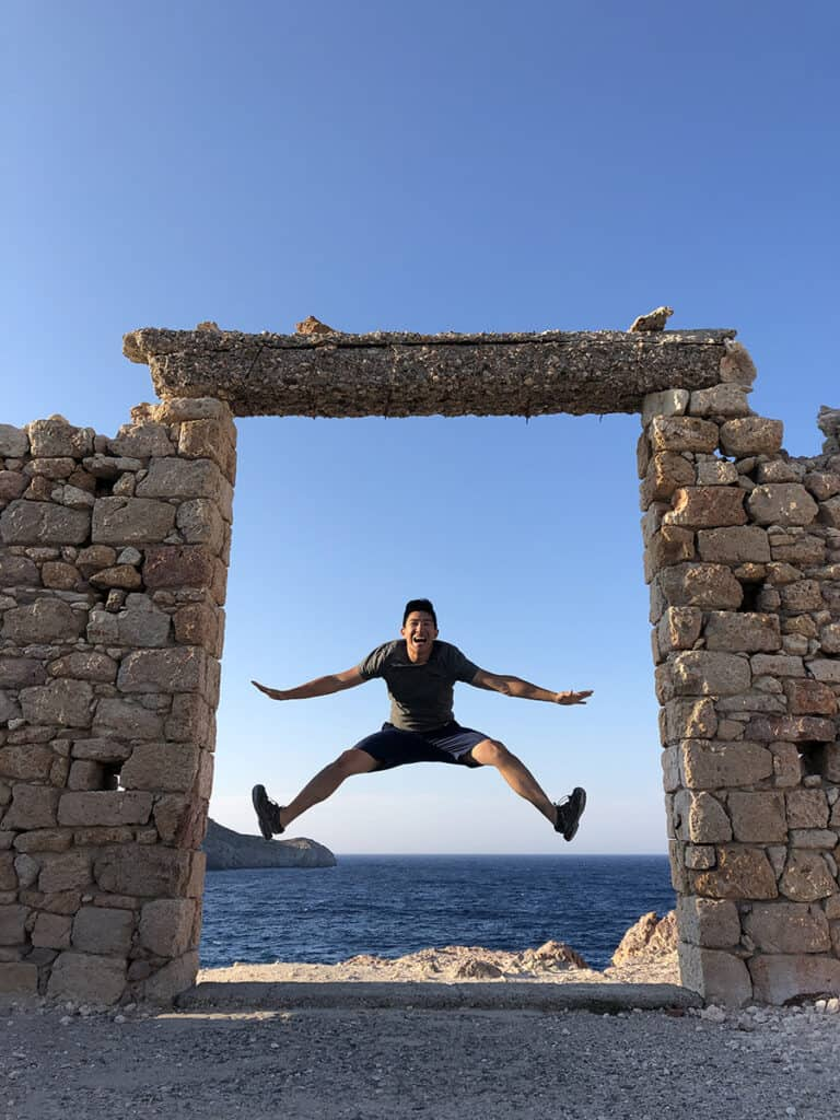 jumping in a brick door opening with sea behind in milos greece