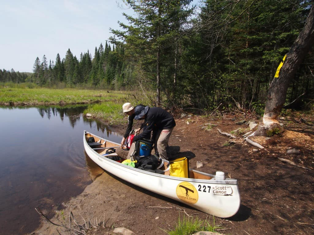 daily routine of unloading and reloading canoe in portage trip