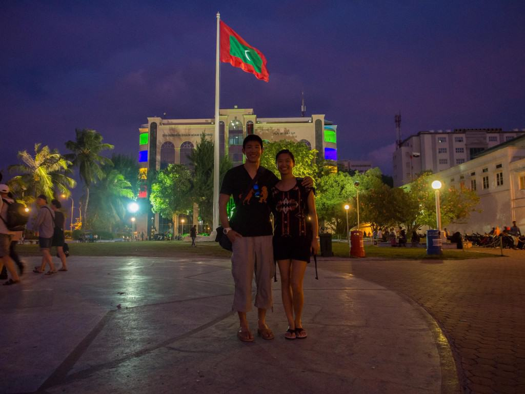 Us in front of the police station and huge flag of the Republic of Maldives.