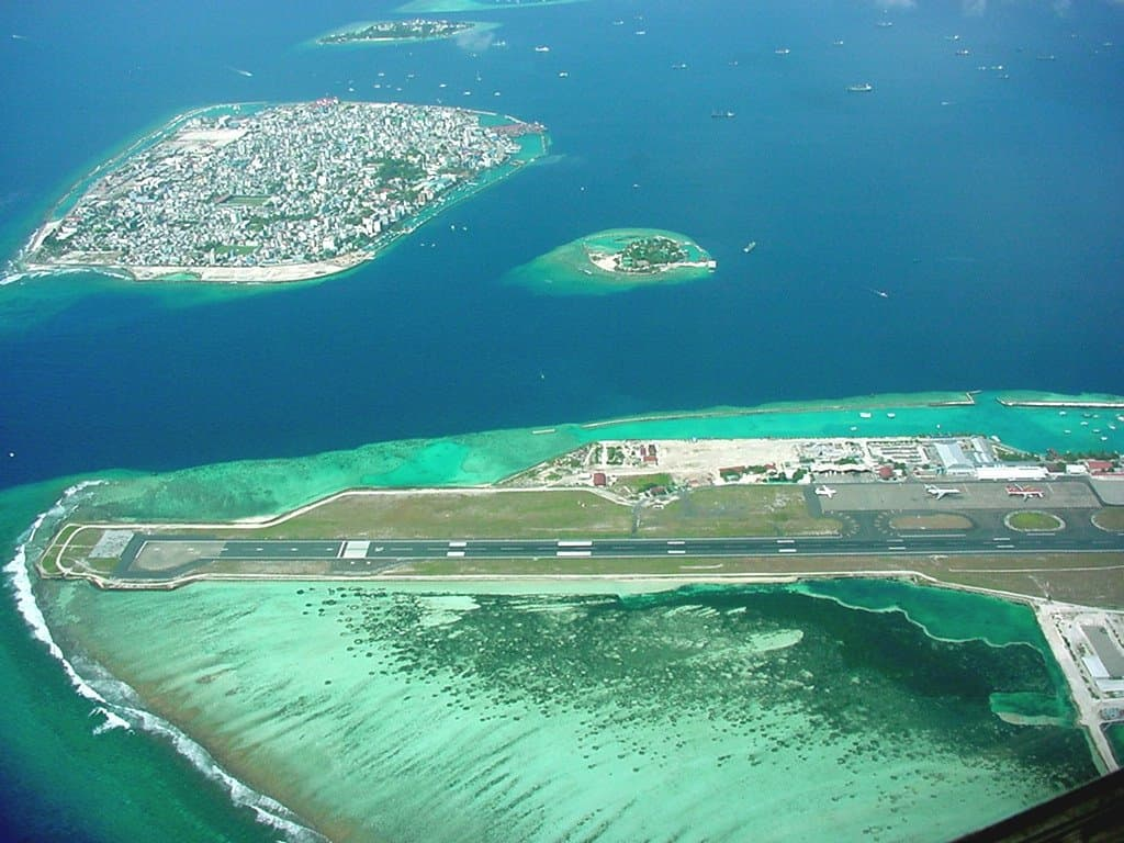 Male International Airport with the capital city of Malé behind.