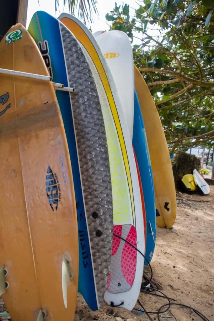 stack of surf boards on the sand at macao surf camp