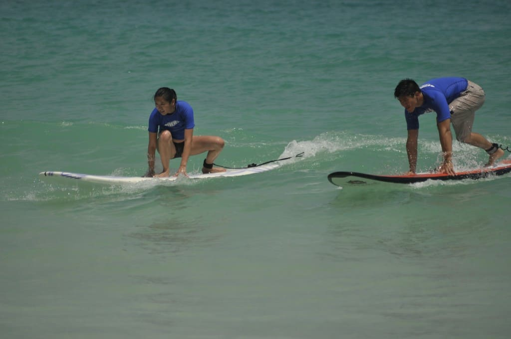 two surfers in the middle of getting up on their surf boards on macao beach