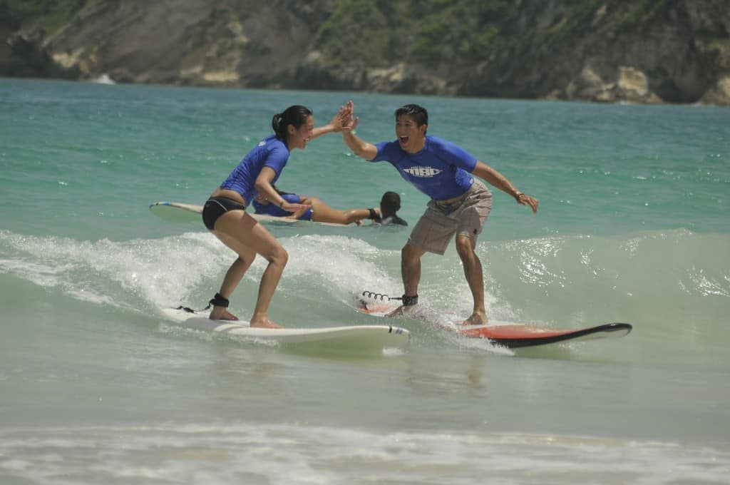 two surfers high fiving while surfing with macao surf camp