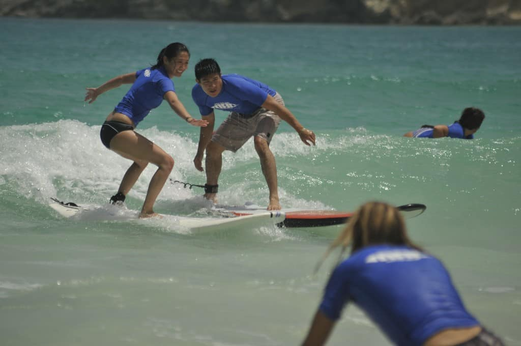 couple surfing together with macao surf camp near punta cana
