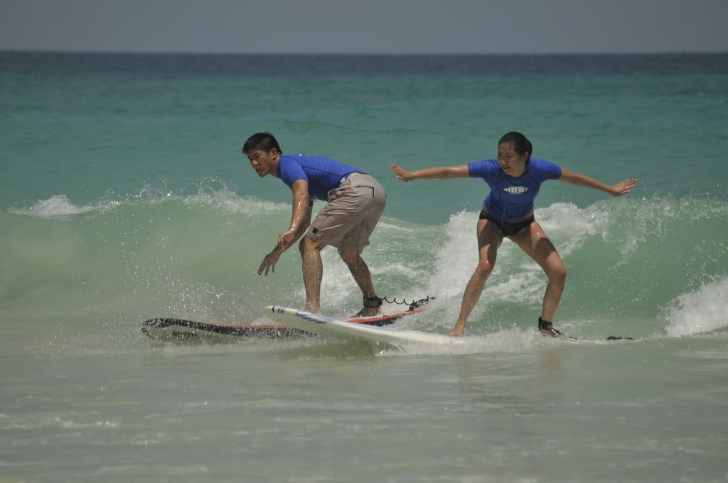 asian male and female surfing in the dominican republic with macao surf camp