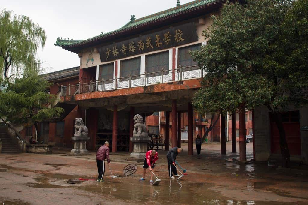 One of the oldest and largest Shaolin Kung Fu schools in the area with 30,000 students here.  The kids are put to work after the rain, pushing the water into the sewer drain.