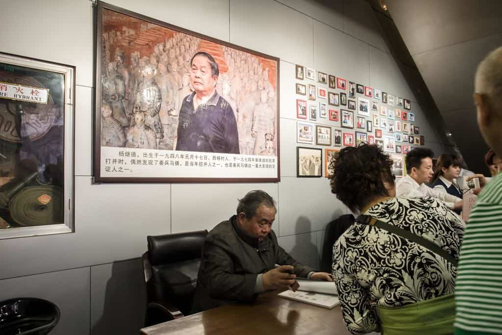 One of the farmers that discovered the site is now on celebrity duty, signing expensive tourist books.