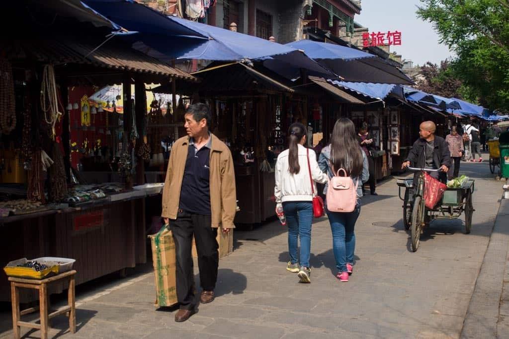 Umbrella'd stalls set up on both sides of the street.