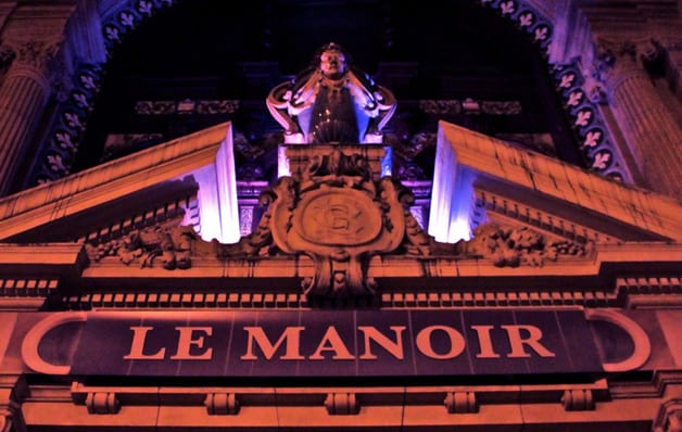 entrance to le manoir in paris in dark red and purple light