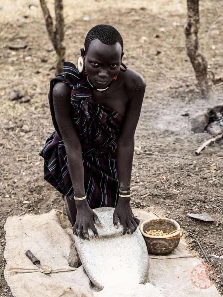 haunted eyes of mursi tribe woman grinding sorghum in omo valley ethiopia