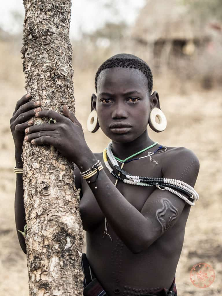 mursi tribe girl standing by a tree in omo valley ethiopia photo essay