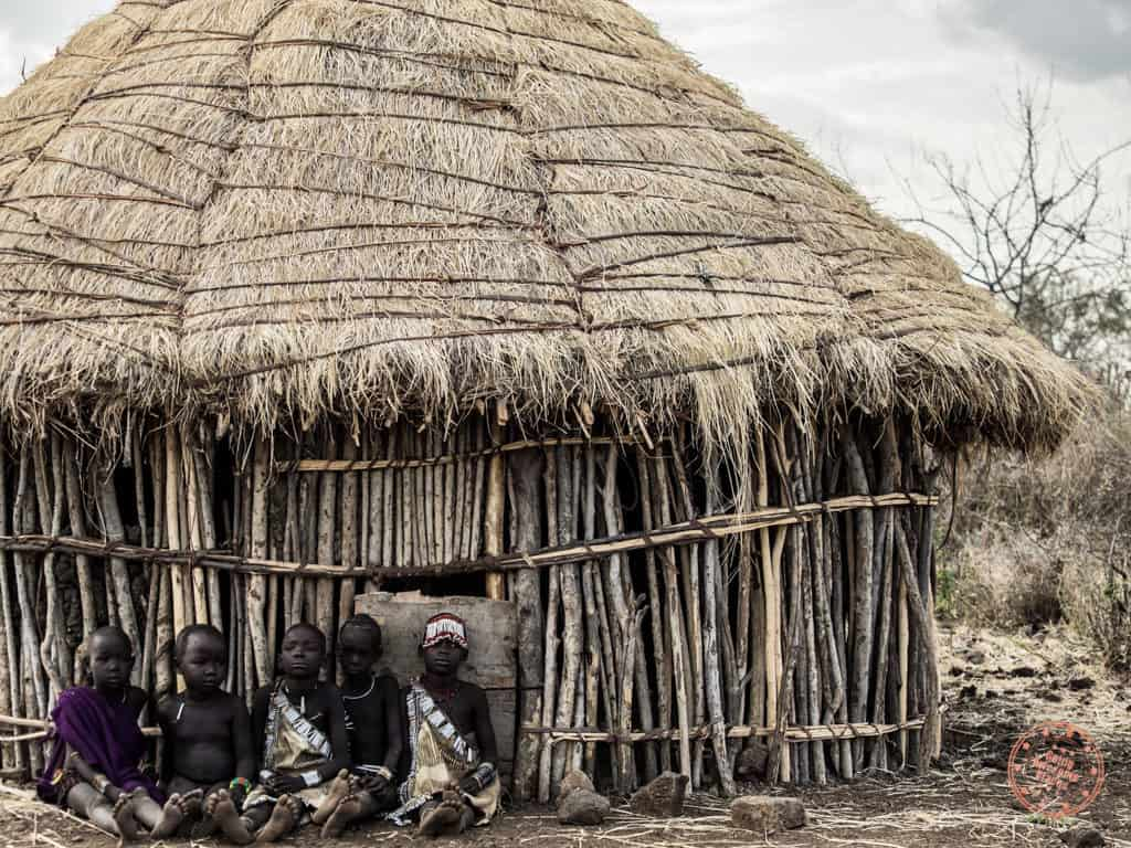 mursi tribe children in front of a hut in omo valley ethiopia