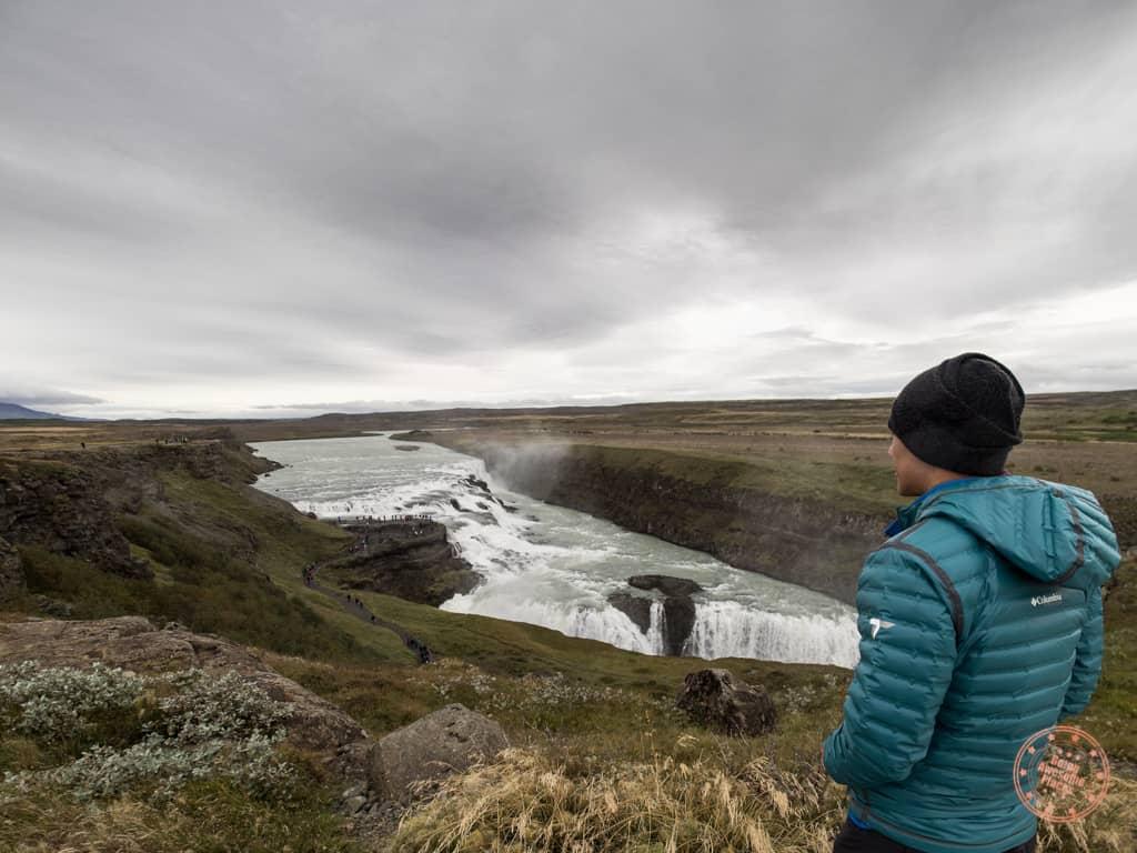 man watching gullfoss waterfall in iceland golden circle road trip
