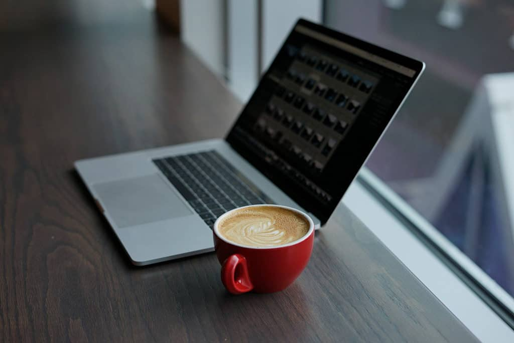laptop and latte in a red cup when building your itinerary