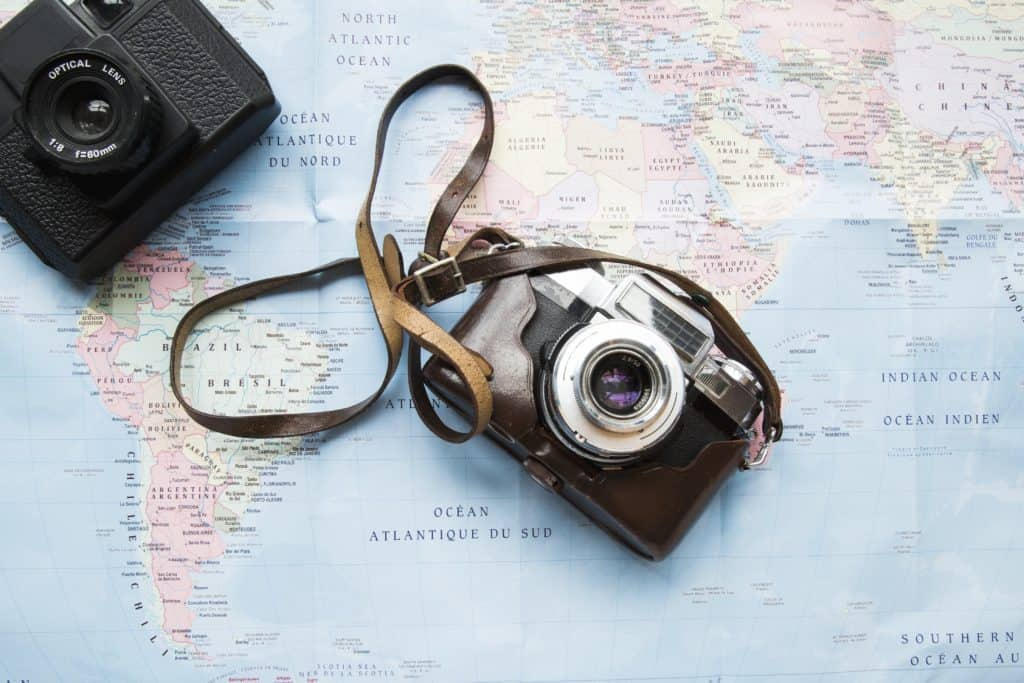 two cameras on top of a map in trip planning process