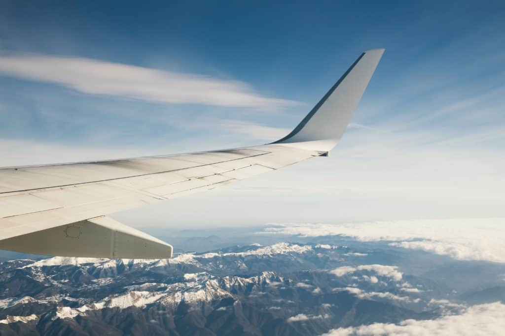 airline plane wing flying over mountains