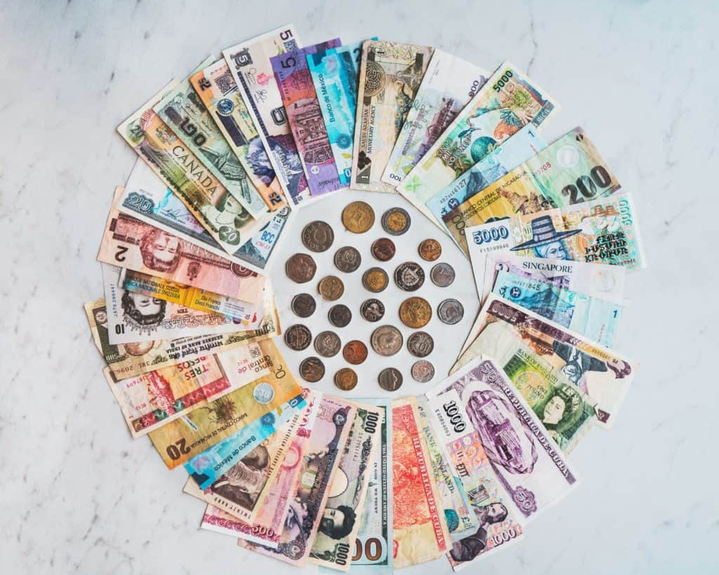 a circle of currency from around the world including bills and coins on marble counter