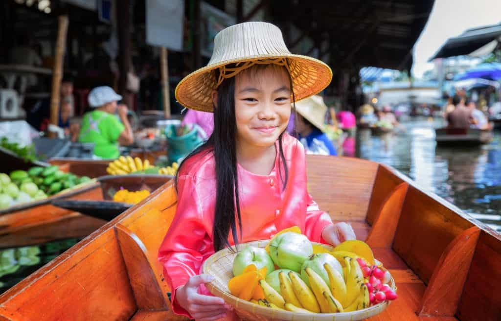 Chikd sit on the boat and hold the fruit basket in Traditional floating market , Thailand.