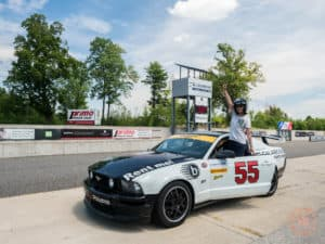 posing with mustang race car at calabogie motorsports park