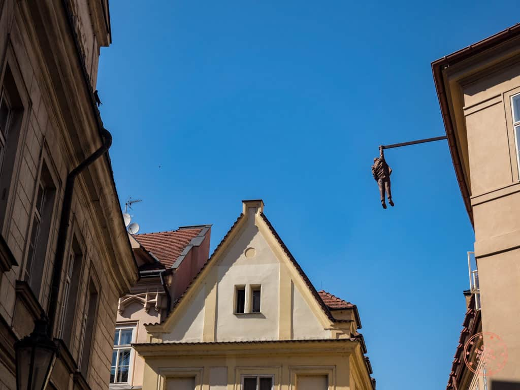 man hanging out sculpture in prague by david cerny