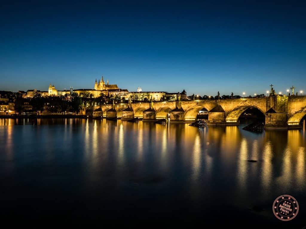 classic prague photograph of the charles bridge lit up at night