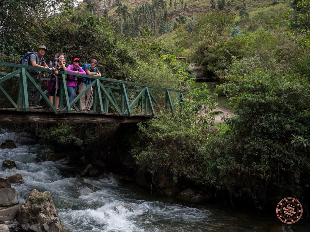 group of friends hiking inca trail on bridge with river underneath