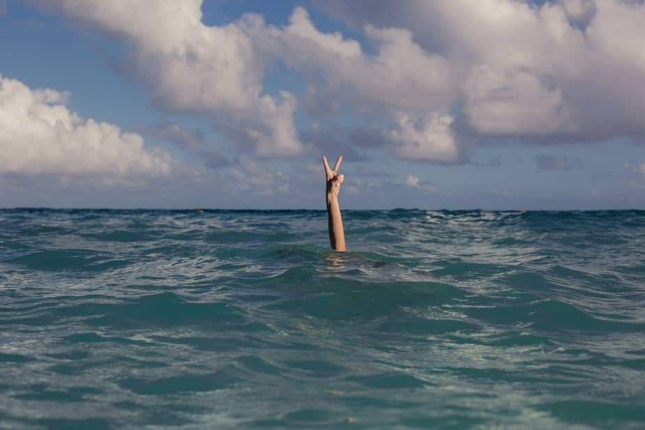 peace sign from ocean with person under water