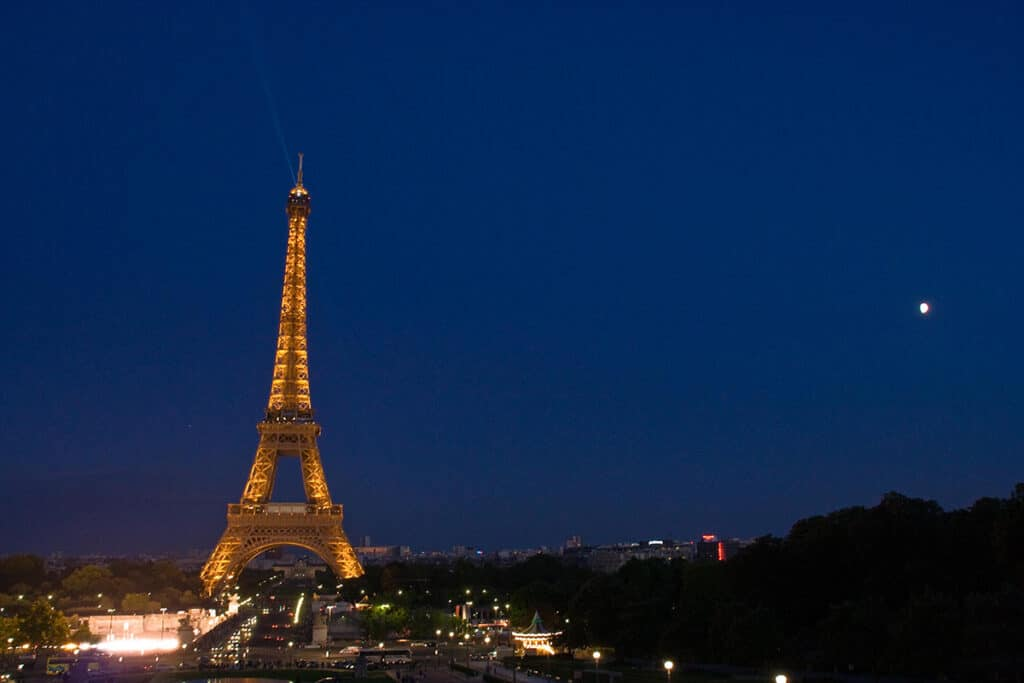 wide shot of the eiffel tower lit up in the evening with the moon in view and the rest of the city of paris