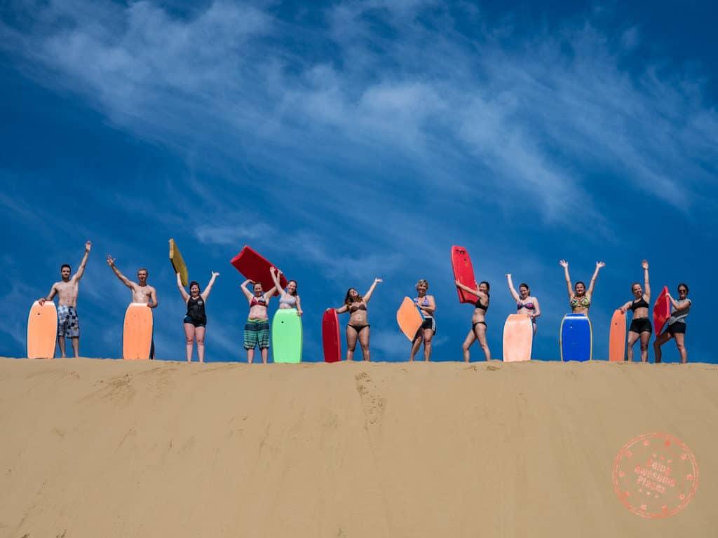 sandboarding flying kiwi group photo adventure tour new zealand