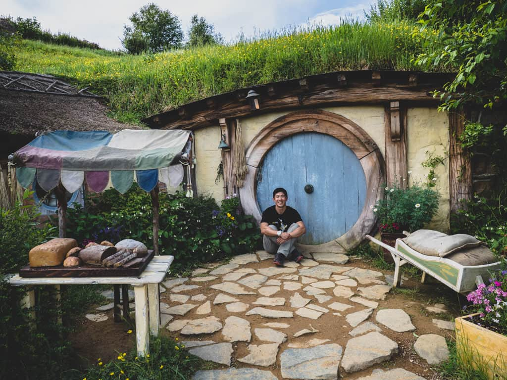 going awesome places sitting in front of a hobbit hole in new zealand