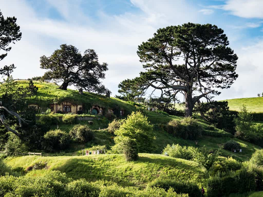 wide angle view of hobbiton movie set from across the lake in new zealand trip