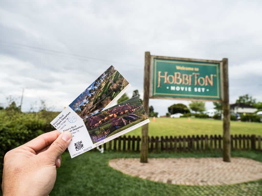 visit hobbiton movie set tickets in front of sign