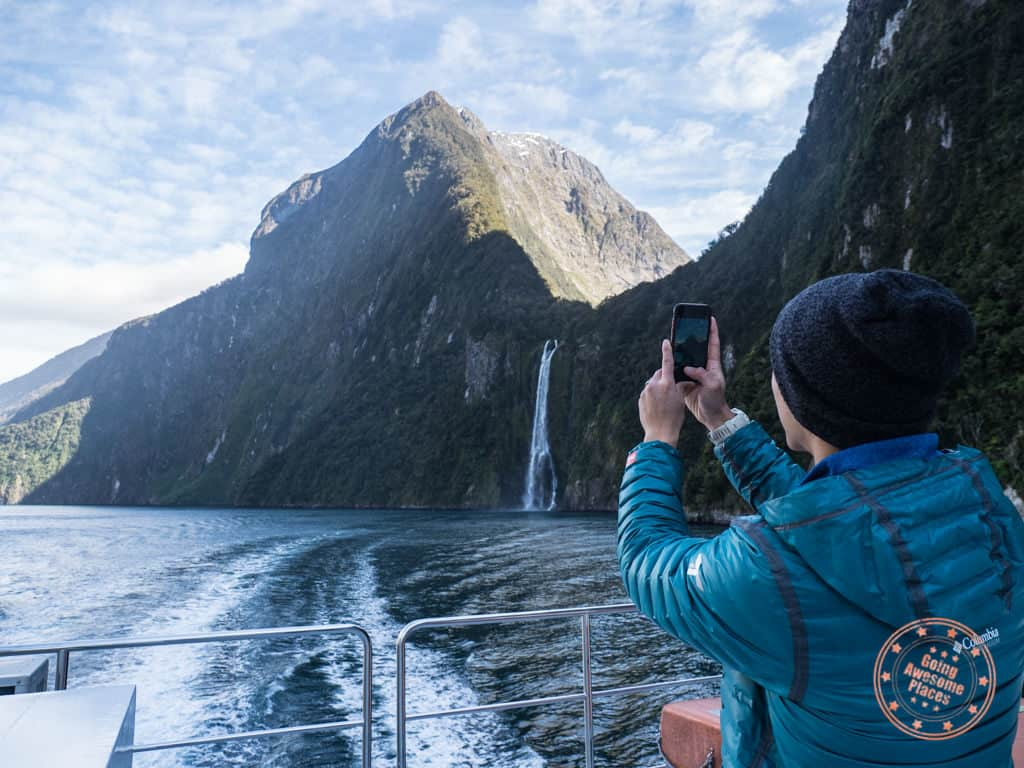 taking phone photos of milford sound on guided new zealand cruise