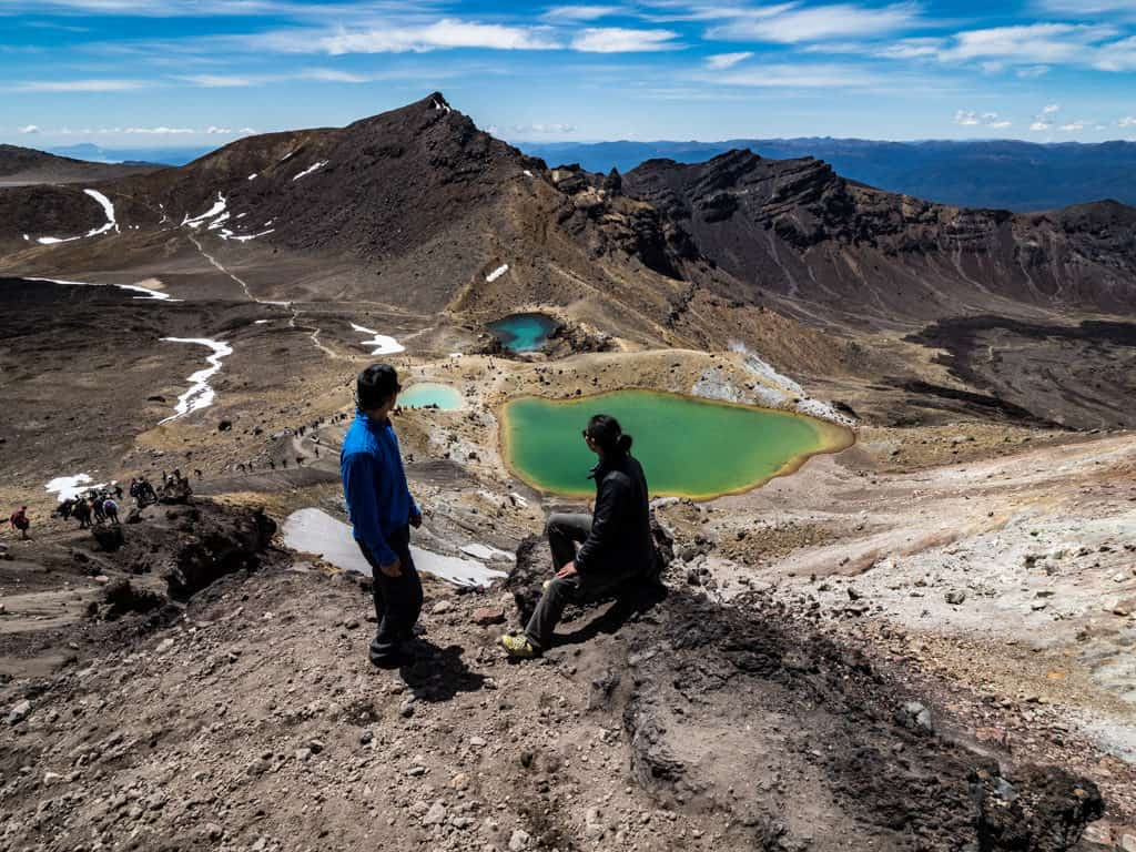 tongariro crossing with one male and one female hiker looking out towards emerald lakes below