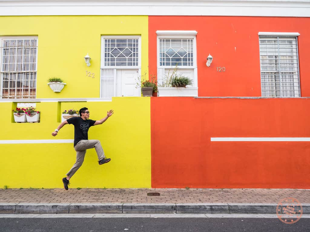jumping in front of bo kaap neighbourhood colourful houses in cape town