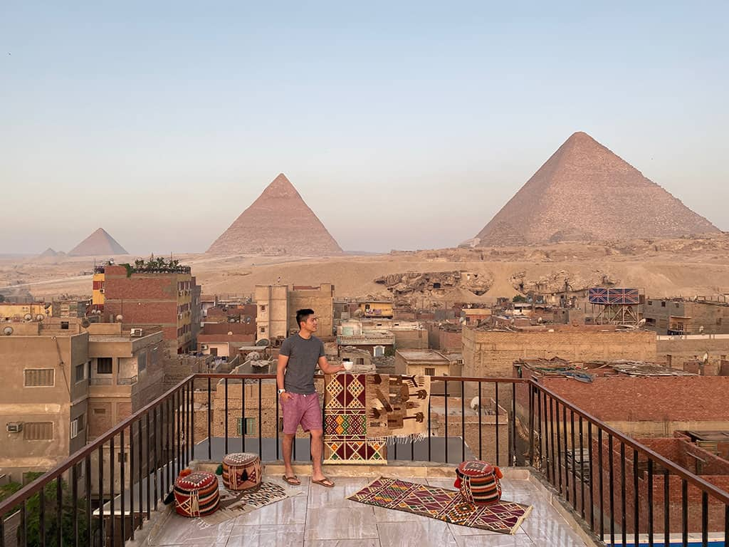 man standing on rooftop with pyramids of giza in the background