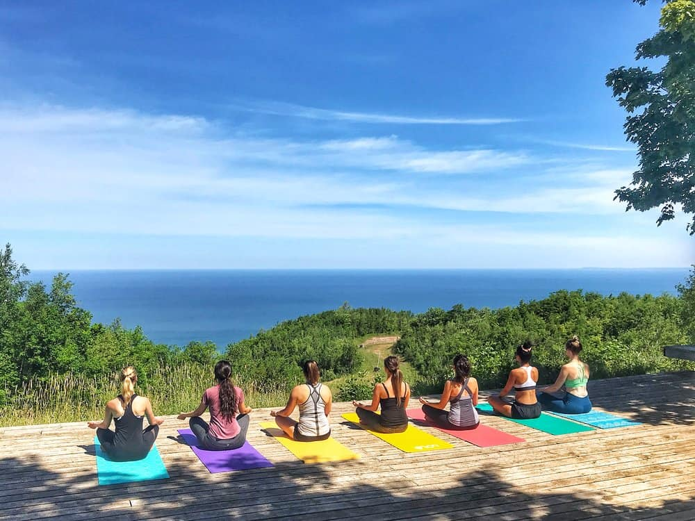 8 women doing yoga with view of forest and lake in wellness retreat in ontario