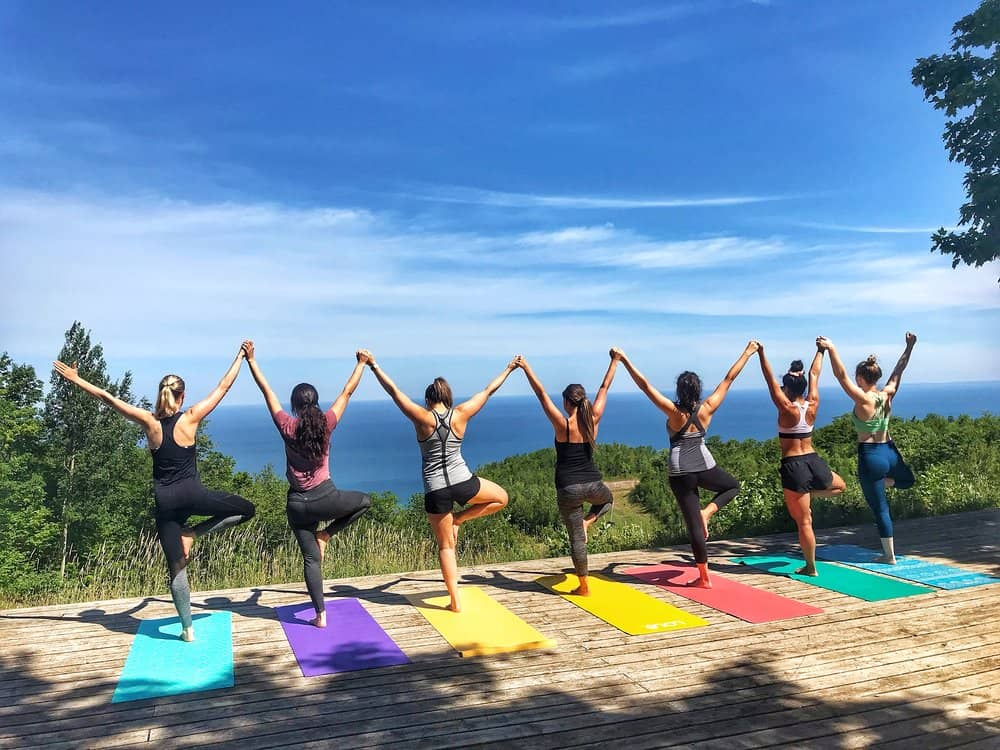 7 women holding yoga pose while holding each others hands in hike and yoga with a view wellness retreat