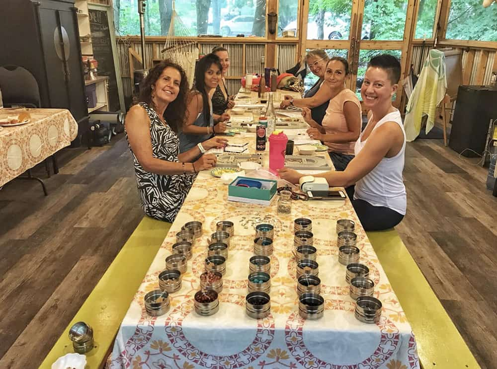 6 women on table in a mala making workshop with boardshorts and boots