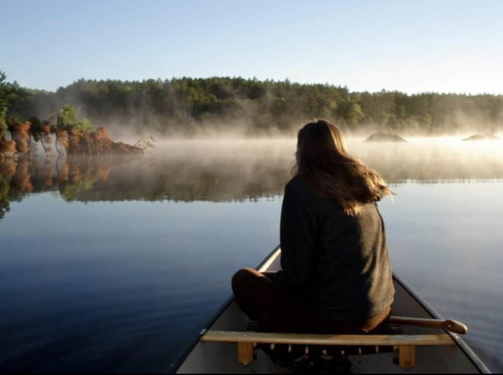 natures harmony woman on canoe looking out to the mist of the lake