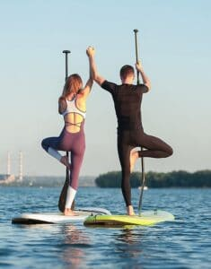 man and woman doing yoga pose on stand up paddleboard with full moon sup yoga