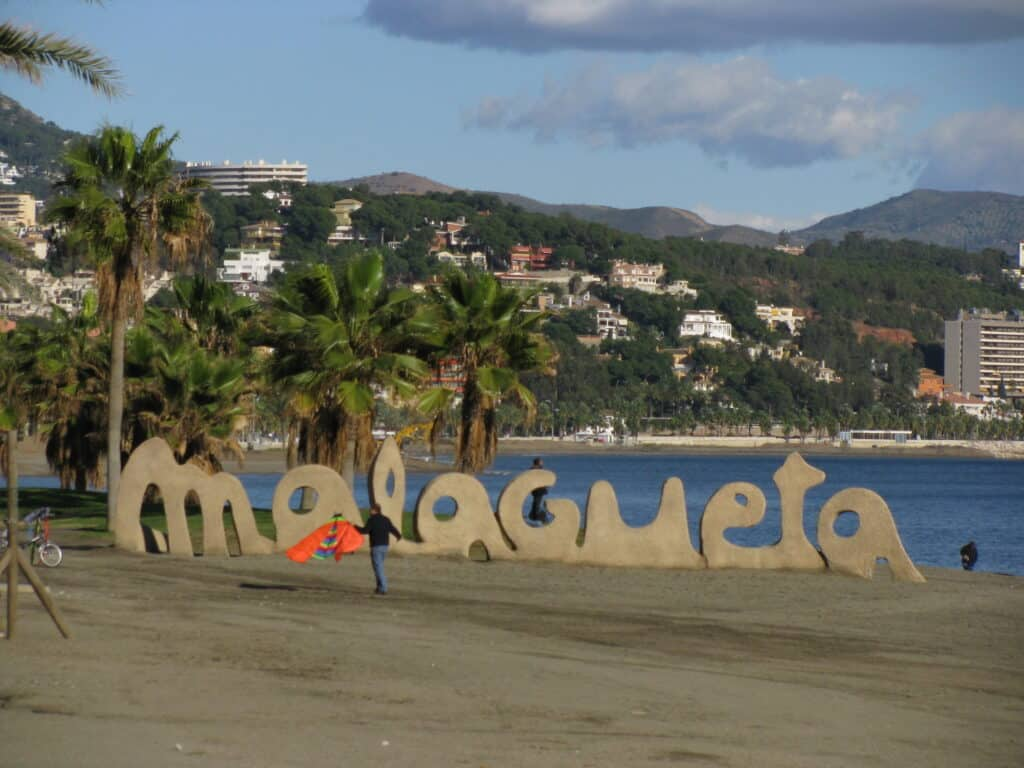 Malagueta beach with the name Malagueta shaped in sand in front of palm trees and the ocean.