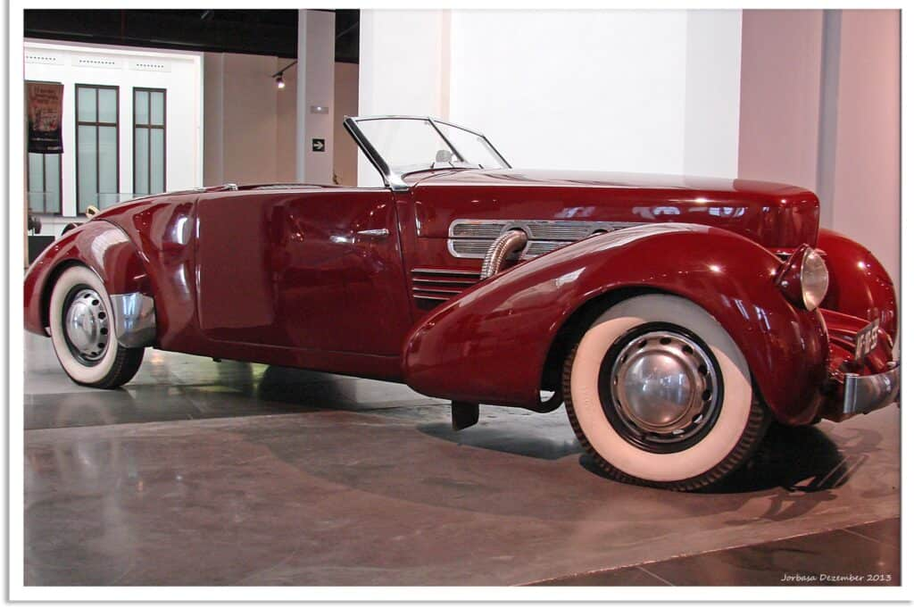 A beautiful red antique car with white tires and no top.
