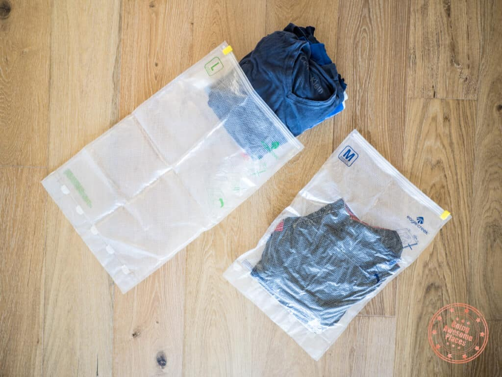 two compression sac next to each other with a stack of t-shirts about to be inserted in the large bag