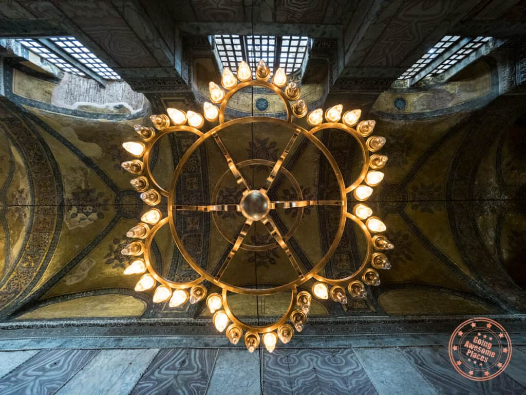 looking up at the golden chandelier and ceiling of hagia sophia in istanbul