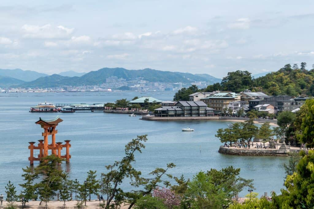 ocean view of Hiroshima city with mountains and houses in the distance.
