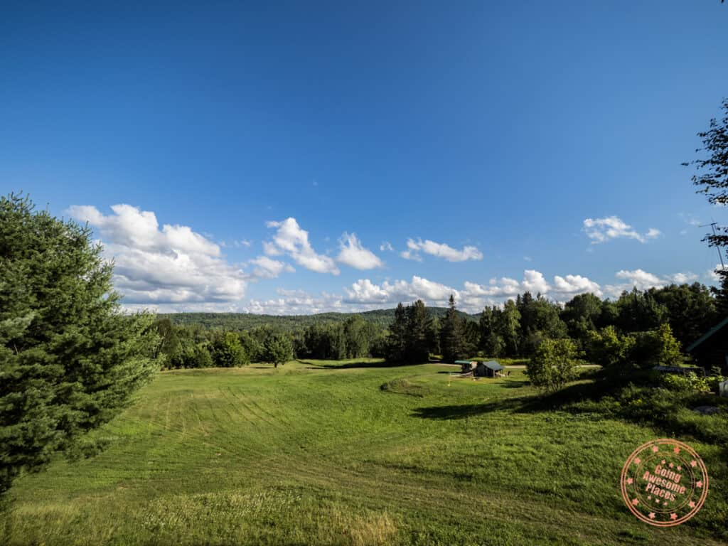 green hills with trees and laurentian mountains in the background at nature's harmony eco-lodge