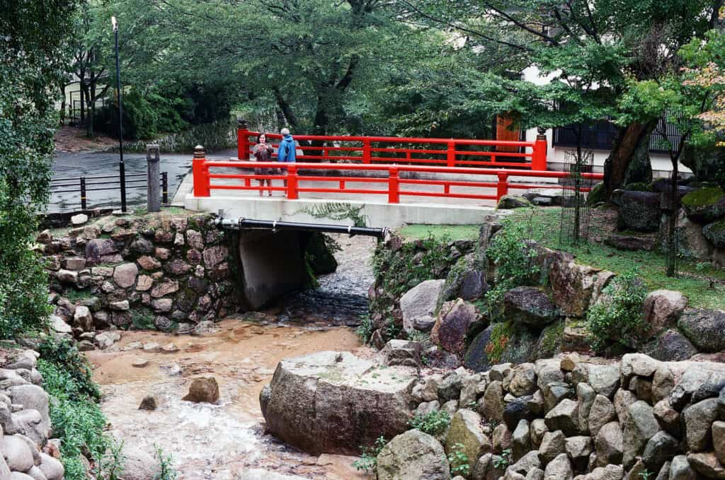 bridge with bright red railings over top a small creek in a park new Japan University